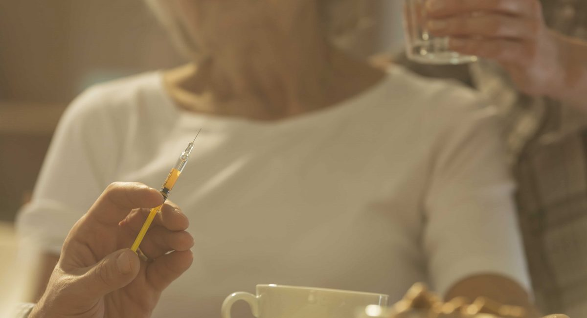 Close-up of syringe with medicine for sick elderly woman